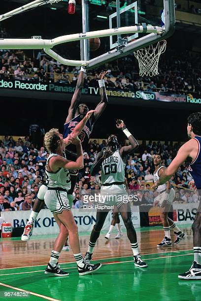 Patrick Ewing of the New York Knicks shoots a layup against Larry Bird and Robert Parish of the Boston Celtics during a game played in 1987 at the...