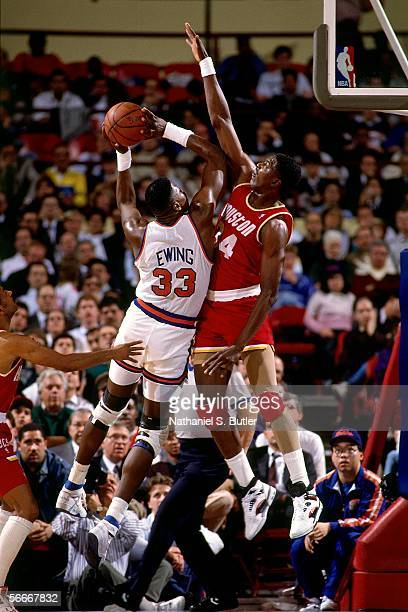 Patrick Ewing of the New York Knicks shoots over Hakeem Olajuwon of the Houston Rockets circa 1990 at Madison Square Garden in New York New York NOTE...