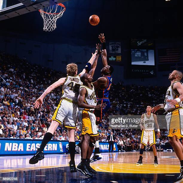 Patrick Ewing of the New York Knicks shoots over Rik Smits and Dale Davis of the Indiana Pacers in Game Two of the Eastern Conference Finals during...