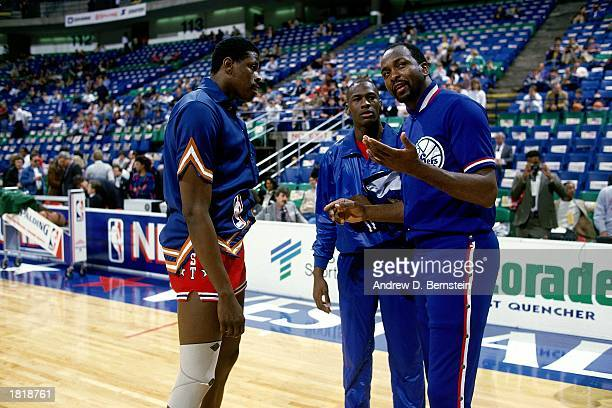 Patrick Ewing of the New York Knicks talks with fellow Eastern Conference AllStars Moses Malone of the Philadelphia 76ers and Michael Jordan of the...