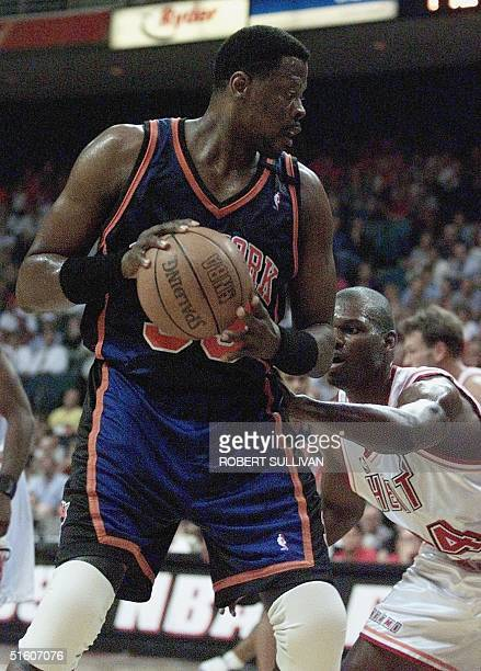Patrick Ewing of the New York Knicks works against Jamal Mashburn of the Miami Heat in first quarter action 10 May 1999 during game two of their...
