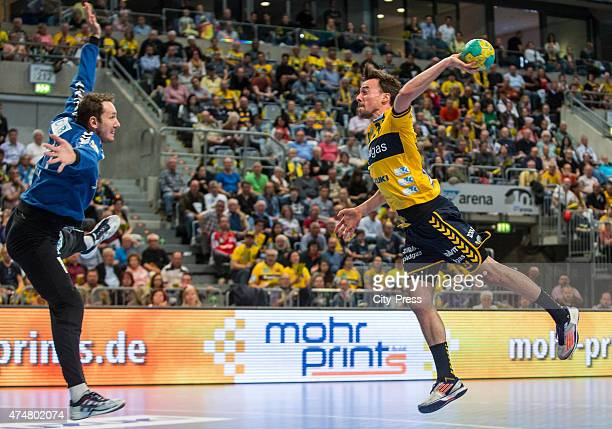 Patrick Groetzki of the RheinNeckar Loewen throws the ball against Petr Stochl of Fuechse Berlin during the game between RheinNeckar Loewen Mannheim...