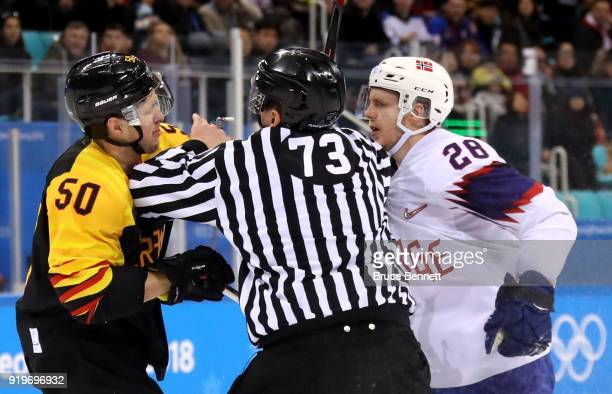 Patrick Hager of Germany and Niklas Roest of Norway are separated by a referee in the second period during the Men's Ice Hockey Preliminary Round...