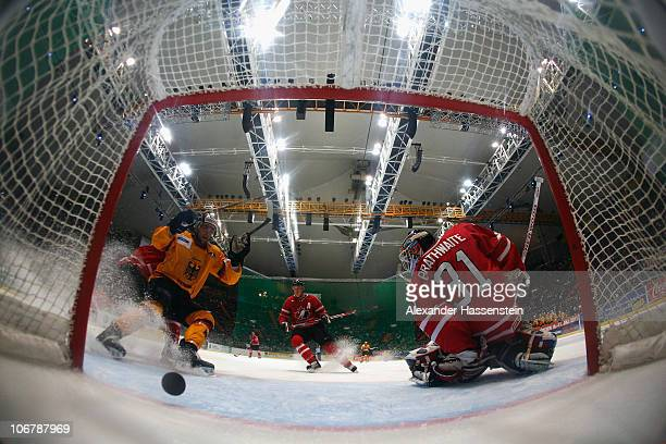Patrick Hager of Germany celebrates the 4th team goal whilst Fred Brathwaite, goalie of Canada reacts during the German Ice Hockey Cup 2010 first...