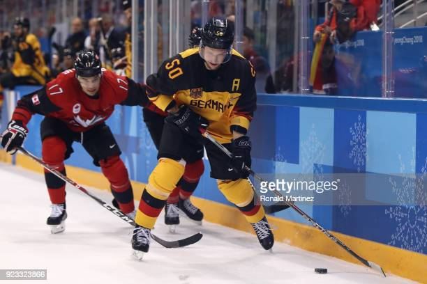 Patrick Hager of Germany controls the puck against Rene Bourque of Canada in the first period during the Men's Play-offs Semifinals on day fourteen...