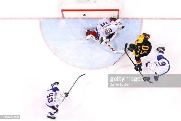 Patrick Hager of Germany scores against Lars Haugen of Norway in the second period during the Men's Ice Hockey Preliminary Round Group B game on day...