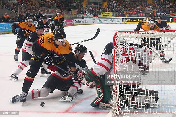 Patrick Hager of Germany skates with Chris Abbott of Canada and his goalie Chris Mason during match 6 of the Deutschland Cup 2014 between Canada and...