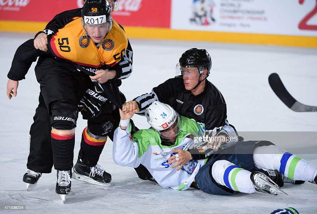 Patrick Hager of Team Germany, Rok Ticar of Team Slovenia and linesman Seedo Janssen during the game between Germany and Slovenia on april 29, 2015 in Berlin, Germany.