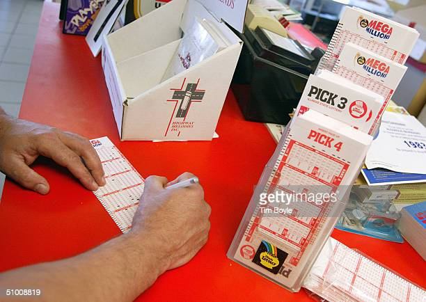 Patrick Herdeman from Wauwatosa Wisconsin fills out his Mega Millions lottery ticket June 29 2004 at a Citgo gas station in Russell Illinois on the...