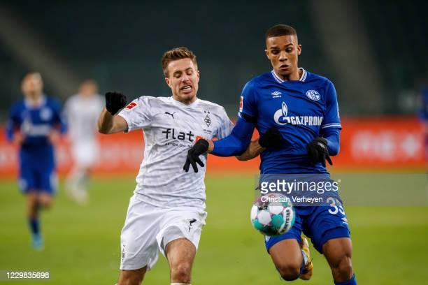 Patrick Herrmann of Borussia Moenchengladbach and Malick Thiaw of FC Schalke 04 battle for the ball during the Bundesliga match between Borussia...