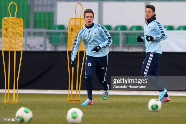 Patrick Herrmann of Germany plays the ball with his team mate Mesut Oezil during a training session of the German national footall team at at...
