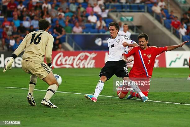 Patrick Herrmann of Germany scores his team's first goal against Georgi Schennikov and goalkeeper Aleksandr Filtsov of Russia during the UEFA...