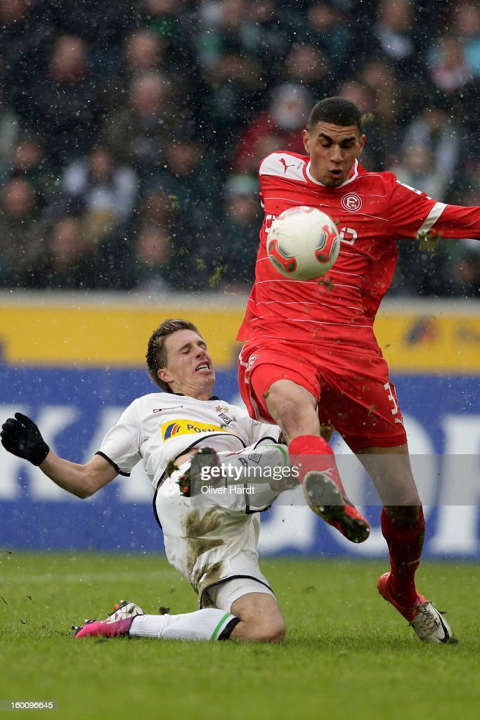 Patrick Herrmann (L) of Gladbach and Leon Balogun (R) of Duesseldorf battle for the ball during at Bundesliga match between VfL Borussia Moenchengladbach v Fortuna Duesseldorf at Borussia Park Stadium on January 26, 2013 in Moenchengladbach, Germany.
