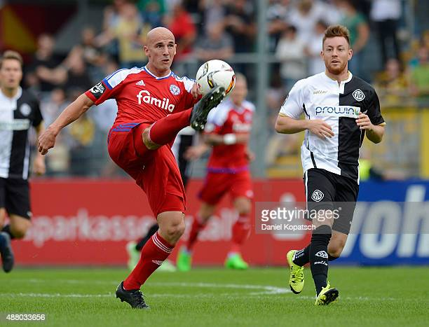 Patrick Herrmann of Kiel is challenged by Michael Klauss of Aalen during the third league match between VfR Aalen and Holstein Kiel at ScholzArena on...