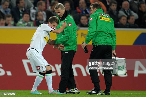 Patrick Herrmann of Moenchengladbach is treated after suffering an injury during the Bundesliga match between Borussia Moenchengladbach and Hamburger...