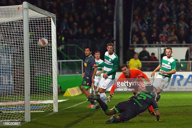 Patrick Herrmann of Moenchengladbach scores his team's third goal against goalkeeper Max Gruen of Greuther Fuerth during the Bundesliga match between...