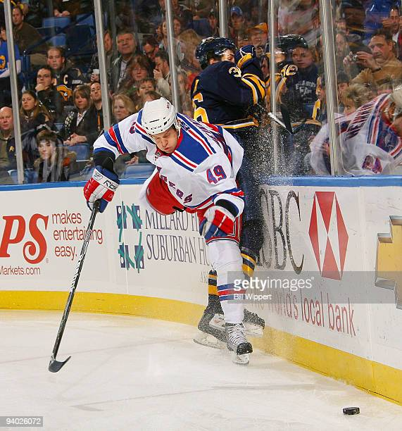 Patrick Kaleta of the Buffalo Sabres get checked into the endboards by Ilkka Heikkinen of the New York Rangers on December 5, 2009 at HSBC Arena in...