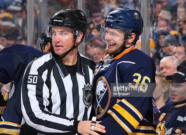 Patrick Kaleta of the Buffalo Sabres laughs while restrained by linesman Scott Cherrey in a game against the Boston Bruins at HSBC Arena on December...