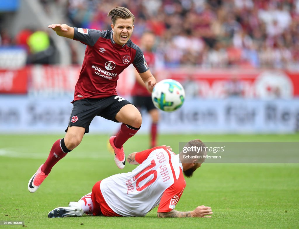 Patrick Kammerbauer of 1. FC Nuernberg jumps over Marvin Knoll of SSV Jahn Regensburg during the Second Bundesliga match between SSV Jahn Regensburg and 1. FC Nuernberg at Continental Arena on August 6, 2017 in Regensburg, Germany.