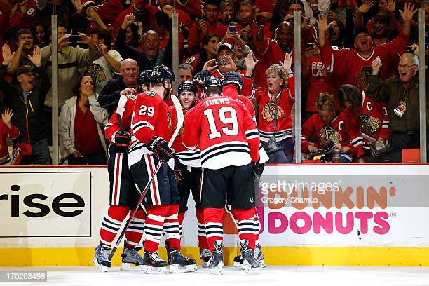 Patrick Kane of the Chicago Blackhawks celebrates with teammates including Bryan Bickell and Jonathan Toews after Kane scored a goal in the third...