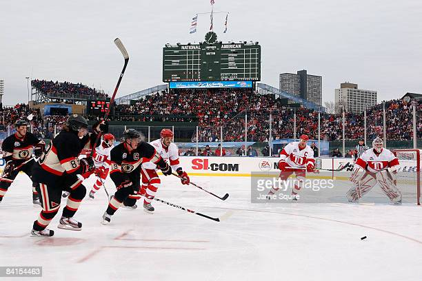 Patrick Kane and Jonathan Toews of the Chicago Blackhawks chase down the puck against the Detroit Red Wings during the NHL Winter Classic at Wrigley...