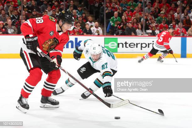 Patrick Kane of the Chicago Blackhawks and Joonas Donskoi of the San Jose Sharks chase the puck in the second period at the United Center on December...