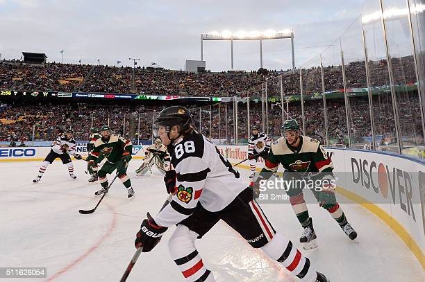 Patrick Kane of the Chicago Blackhawks and Marco Scandella of the Minnesota Wild skate around the boards in the third period of the 2016 Coors Light...