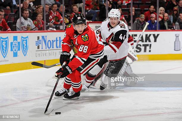 Patrick Kane of the Chicago Blackhawks approaches the puck ahead of Kevin Connauton of the Arizona Coyotes in the second period of the NHL game at...