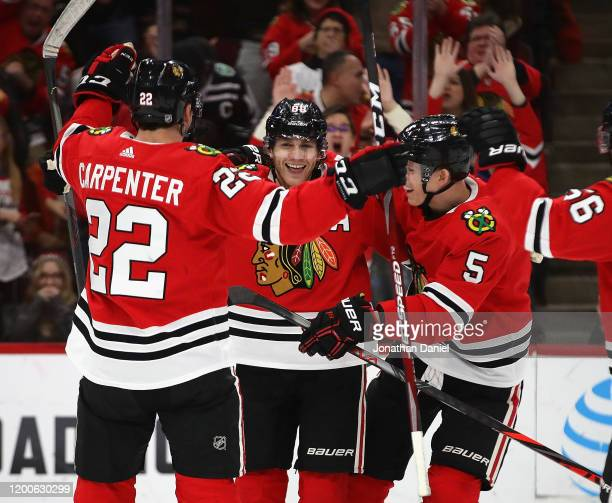 Patrick Kane of the Chicago Blackhawks celebrates his 1000th career point on an assist on a goal by Brandon Saad in the third period with teammates...