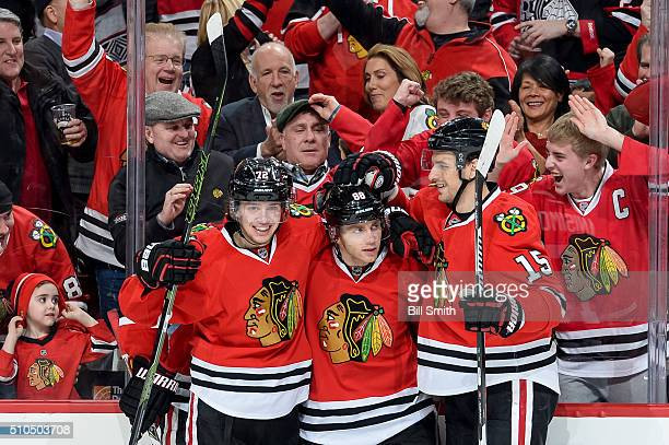 Patrick Kane of the Chicago Blackhawks celebrates with Artemi Panarin and Artem Anisimov after scoring in the third period of the NHL game against...