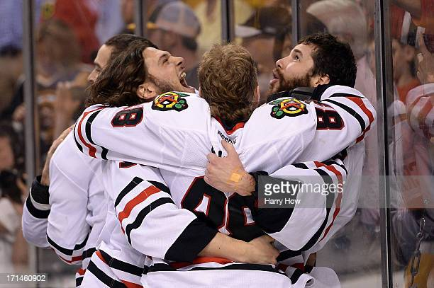 Patrick Kane of the Chicago Blackhawks celebrates with teammate Daniel Carcillo and Corey Crawford after defeating the Boston Bruins in Game Six of...
