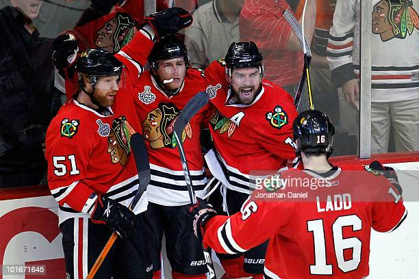 Patrick Kane of the Chicago Blackhawks celebrates with teammates Brian Campbell, Patrick Sharp and Andrew Ladd after scoring a goal in the second...