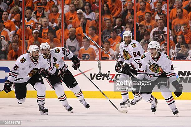 Patrick Kane of the Chicago Blackhawks celebrates with teammates Andrew Ladd Patrick Sharp and Nick Boynton after scoring a goal in overtime to...