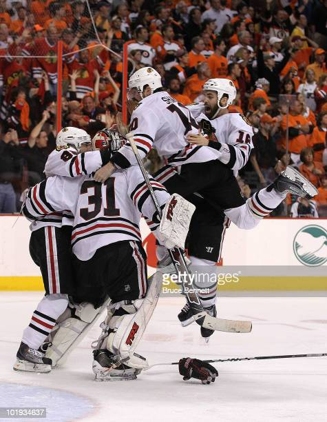 Patrick Kane of the Chicago Blackhawks celebrates with teammates Andrew Ladd Patrick Sharp and Antti Niemi after scoring a goal in overtime to defeat...
