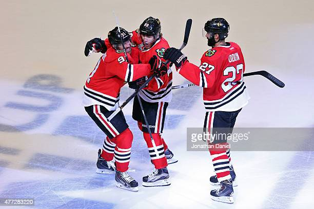 Patrick Kane of the Chicago Blackhawks celebrates with teammates Johnny Oduya and Brad Richards after scoring a goal in the third period against the...