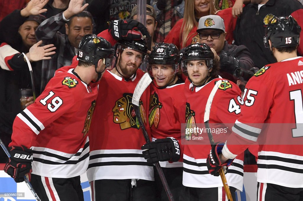 Patrick Kane #88 of the Chicago Blackhawks (middle) celebrates with teammates, including Erik Gustafsson #56 and Vinnie Hinostroza #48, after scoring the game-winning goal against the Boston Bruins in the third period at the United Center on March 11, 2018 in Chicago, Illinois.