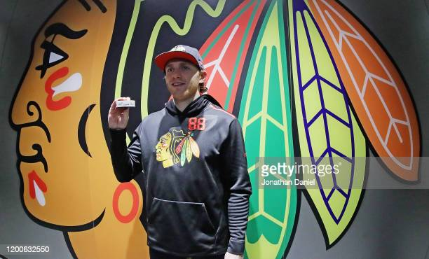 Patrick Kane of the Chicago Blackhawks displays the puck that was used on his 1000th career point an assist on a goal by Brandon Saad against the...
