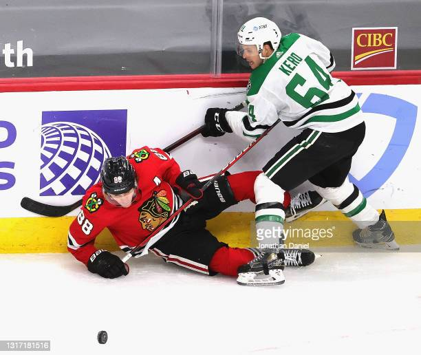 Patrick Kane of the Chicago Blackhawks gets knocked to the ice by Tanner Kero of the Dallas Stars as they battle for the puck along the boards at the...