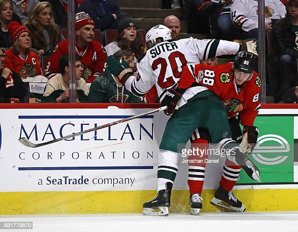 Patrick Kane of the Chicago Blackhawks gets tangled up with Ryan Suter of the Minnesota Wild along the boards at the United Center on January 15 2017...