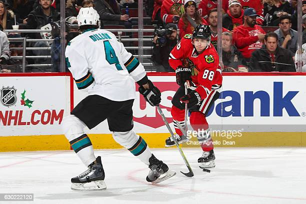Patrick Kane of the Chicago Blackhawks hits the puck toward Brenden Dillon of the San Jose Sharks in the second period at the United Center on...