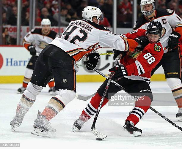 Patrick Kane of the Chicago Blackhawks is hit while advancing the puck by Josh Manson of the Anaheim Ducks at the United Center on February 13 2016...