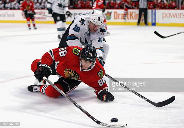 Patrick Kane of the Chicago Blackhawks is knocked to the ice by Patrick Marleau of the San Jose Sharks at the United Center on December 20 2015 in...