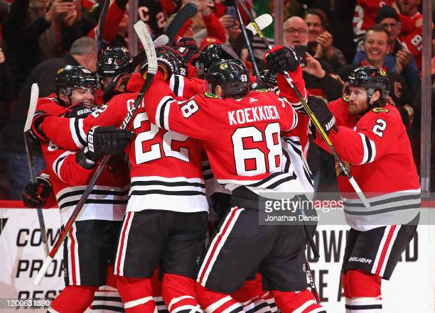 Patrick Kane of the Chicago Blackhawks is mobbed by teammates after getting his 1000th career point on an assist on a goal by Brandon Saad in the...