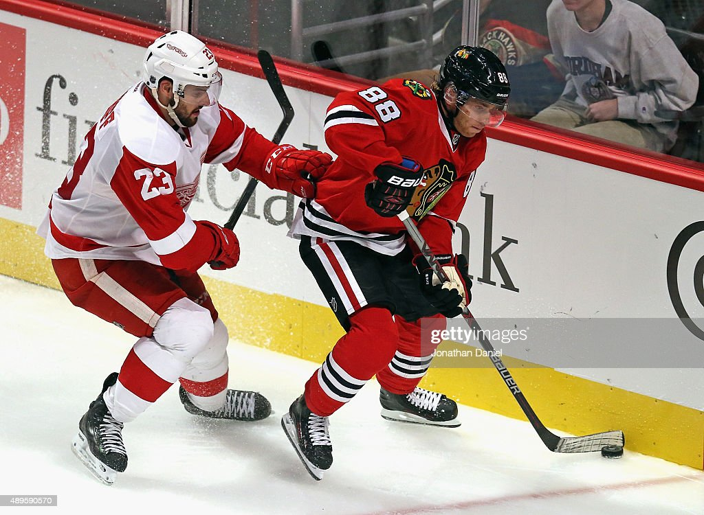 Patrick Kane #88 of the Chicago Blackhawks is pressured by Brian Lashoff #23 of the Detroit Red Wings during a preseason game at the United Center on September 22, 2015 in Chicago, Illinois. The Blackhawks defeated the Red Wings 5-4 in overtime.