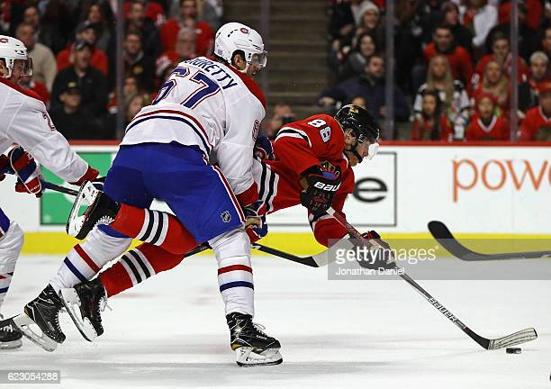Patrick Kane of the Chicago Blackhawks is shoved to the ice by Max Pacioretty of the Montreal Canadiens as he shoots and scores a second period goal...