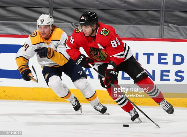 Patrick Kane of the Chicago Blackhawks moves the puck away from Mikael Granlund of the Nashville Predators during the second period at United Center...