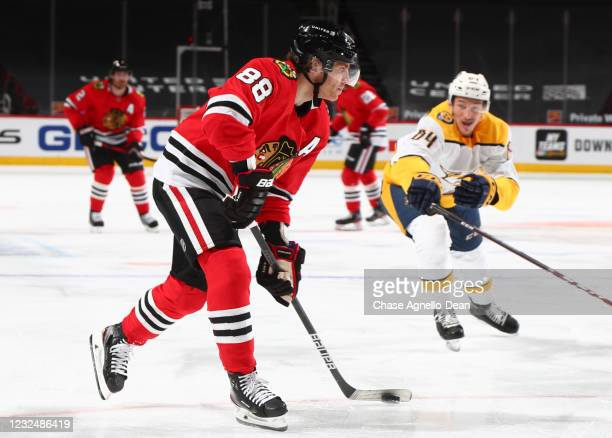 Patrick Kane of the Chicago Blackhawks moves the puck away from Tanner Jeannot of the Nashville Predators in the first period at United Center on...