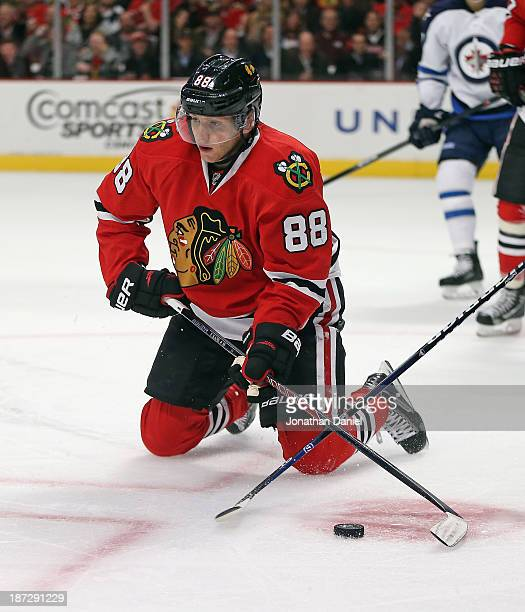 Patrick Kane of the Chicago Blackhawks passes from his knees after getting knocked down against the Winnipeg Jets at the United Center on November 6...