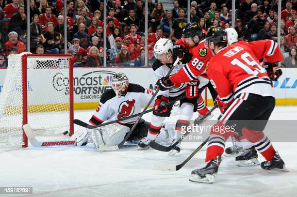 Patrick Kane of the Chicago Blackhawks scores a goal on goalie Cory Schneider of the New Jersey Devils during the NHL game on December 23 2013 at the...