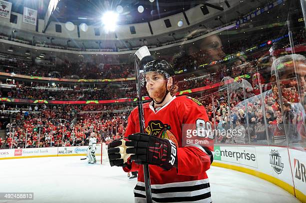 Patrick Kane of the Chicago Blackhawks skates as Chicago mayor Rahm Emanuel and daughter Ilana's reflections show off the glass in Game Five of the...